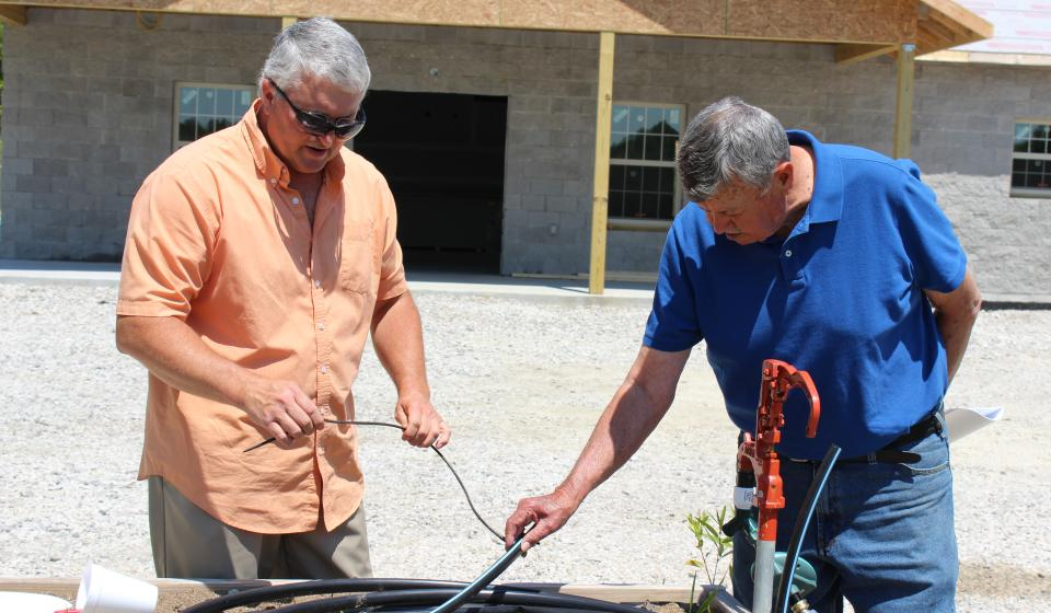 Ted and Jessie discussing irrigation equipment.